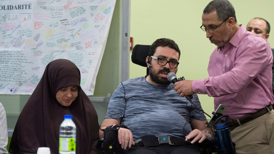 Aymen Derbali, centre, the father of three shot seven times and partly paralyzed in the Quebec City mosque shooting last year, speaks at an event at the Centre Islamique de Quebec, marking the first anniversary of the mosque shooting, Saturday, January 27, 2018 in Quebec City. Derbali's wife Nedra Zahouani, left, sits by his side. (THE CANADIAN PRESS/Jacques Boissinot)