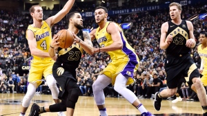 Toronto Raptors guard Fred VanVleet (23) drives between Los Angeles Lakers guard Alex Caruso (4) and Lakers forward Larry Nance Jr. (7) during first half NBA basketball action in Toronto on Sunday, January 28, 2018. (THE CANADIAN PRESS/Frank Gunn)