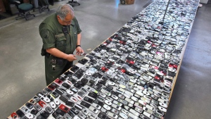 In this April 10, 2009, file photo, Correctional Officer Jose Sandoval inspects one of the more than 2,000 cell phones confiscated from inmates at California State Prison, Solano in Vacaville, Calif. (AP Photo/Rich Pedroncelli, File)