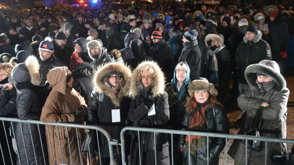 People try to stay warm as they attend a vigil to commemorate the one-year anniversary of the Quebec City mosque shooting, in Quebec City, Monday, Jan. 29, 2018. THE CANADIAN PRESS/Ryan Remiorz