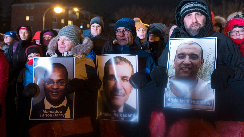 People hold pictures of the victims at a vigil to commemorate the one-year anniversary of the Quebec City mosque shooting, in Quebec City, Monday, Jan. 29, 2018. THE CANADIAN PRESS/Jacques Boissinot
