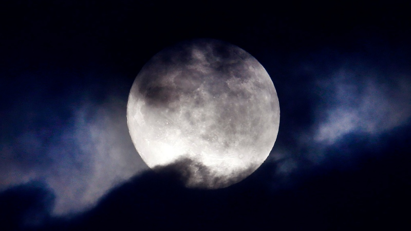 In this file photo, an almost full moon is seen through the clouds over Frankfurt, Germany, Tuesday, Jan. 30, 2018. (AP Photo/Michael Probst)