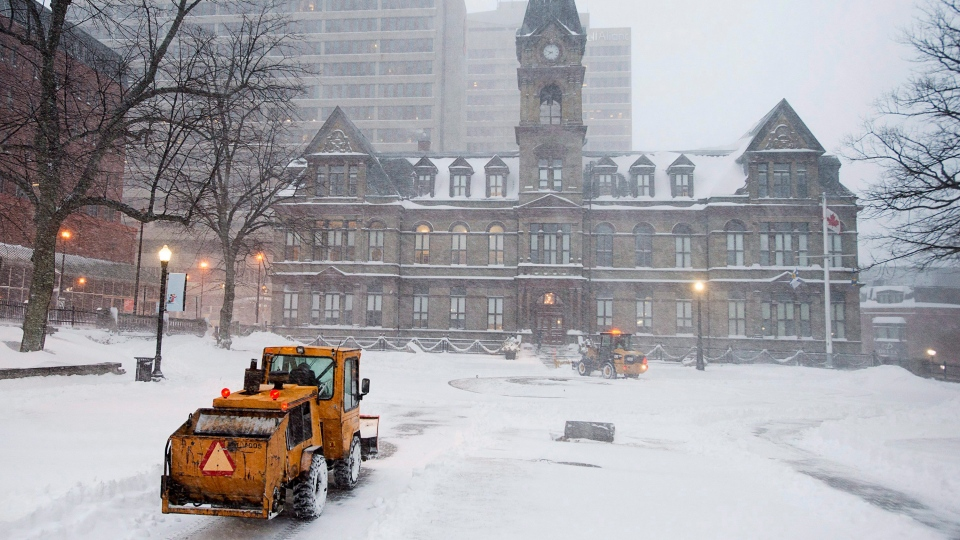 Workers clear snow at city hall in Halifax on Tuesday, Jan. 30, 2018. (THE CANADIAN PRESS/Andrew Vaughan)