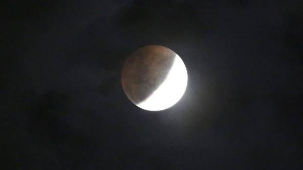 The moon passes into the earth's shadow during a lunar eclipse as seen in Jakarta, Indonesia, Wednesday, Jan. 31, 2018. The moon is putting on a rare cosmic show. It's the first time in 35 years a blue moon has synced up with a supermoon and a total lunar eclipse.(AP Photo/Achmad Ibrahim)