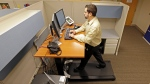 In this file image, Josh Baldonado, an administrative assistant at Brown and Brown Insurance, works at a treadmill desk in the firms offices in Carmel, Ind., Wednesday, Aug. 28, 2013. (AP Photo/Michael Conroy)