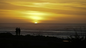 Visitors watch the sunset on the horizon at Hokitika on the West Coast of the South Island of New Zealand on Feb. 27, 2017. (AP Photo/Mark Baker)