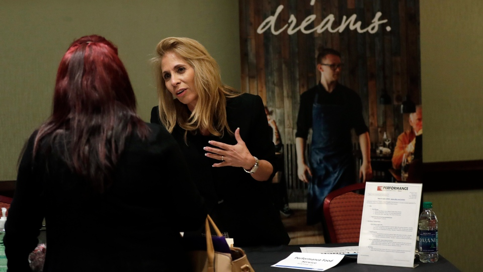 In this Tuesday, Jan. 30, 2018, photo, Grace Ochoa, of Performance Food Service, right, talks with a job applicant at a JobNewsUSA job fair in Miami Lakes, Fla. On Friday, Feb. 2, the U.S. government issues the January jobs report. (AP Photo/Lynne Sladky)