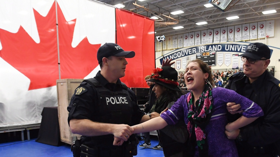 Protesters are carried out of the building by police officers during a public town hall with Prime Minister Justin Trudeau (not shown) in Nanaimo, B.C., on Friday, Feb. 2, 2018. (THE CANADIAN PRESS/Jonathan Hayward(