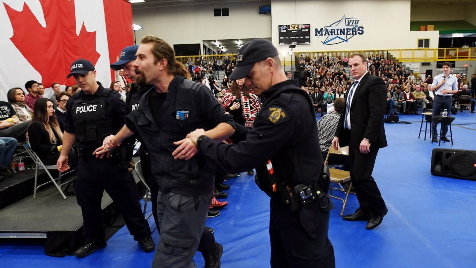 Prime Minister Justin Trudeau, right, looks on as a protester is removed by police officers at a public town hall in Nanaimo, B.C., on Friday, Feb. 2, 2018. (THE CANADIAN PRESS/Jonathan Hayward)