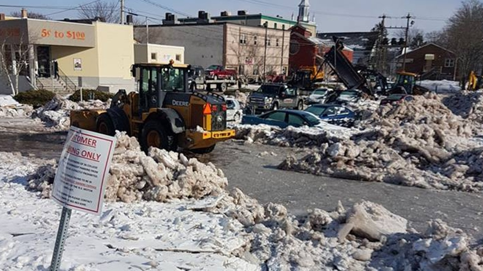 A construction vehicle clears ice near several cars trapped in frozen flash-flood in Antigonish, N.S. (Pete Norman / Facebook)