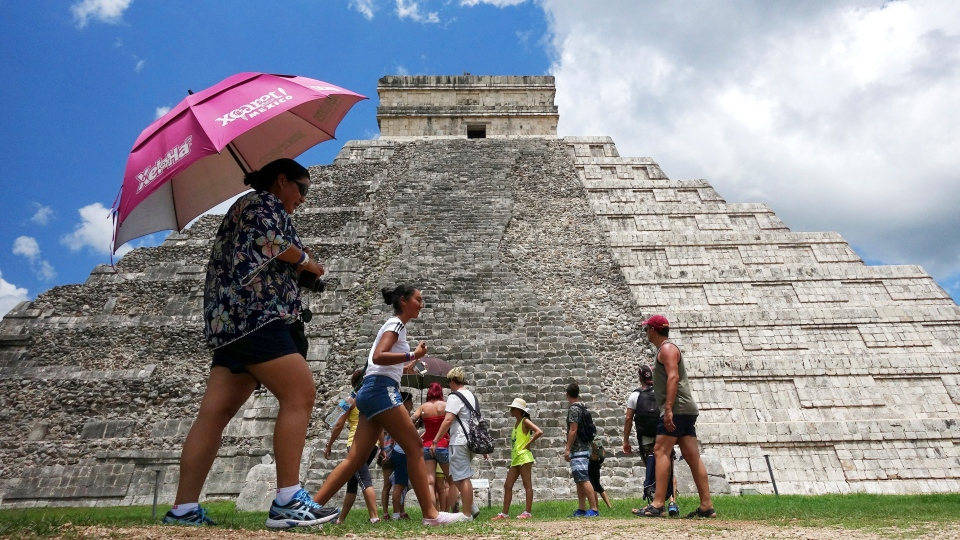 In this July 22, 2016 photo, tourists are dwarfed by El Castillo at the Chichen-Itza ruins in Yucatan, Mexico. The right portion of the pyramid shows the restored pyramid, while the left portion of the pyramid is left unrestored. (AP Photo/Ross D. Franklin)