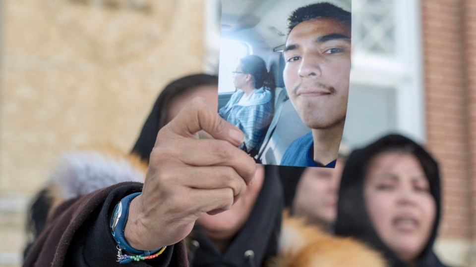 Debbie Baptiste, the mother of Colten Boushie, holds up a picture of her son as she leaves Battleford's Court of Queen's Bench on Monday, Feb. 5, 2018, during a lunch recess on the fifth day of evidence at the trial of Gerald Stanley, the farmer accused of killing the 22-year-old Indigenous man. THE CANADIAN PRESS/Liam Richards