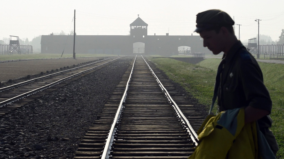 FILE - In this July 29, 2016 photo a man crosses the iconic rails leading to the former Nazi death camp of Auschwitz-Birkenau in Poland. (AP / Alik Keplicz, file)
