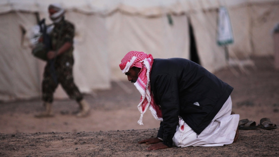 In this Feb. 1, 2018 photograph, an armed Yemeni soldier walks behind another man praying at a camp for those displaced by Yemen's war in Marib, Yemen. (AP / Jon Gambrell)