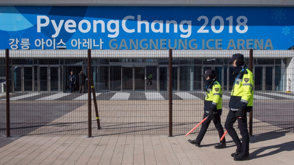 Police officers walk the perimeter of the Gangneung Ice Arena where the figure skating and short track speed skating will be held during the Pyeungchang Winter Olympics Monday, February 5, 2018 in Gangneung. THE CANADIAN PRESS/Paul Chiasson