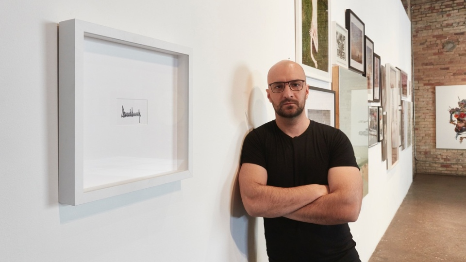 Artist Peter Andrew Lusztyk poses with his sculpture featuring Donald Trump's signature at the Only One Gallery in Toronto.