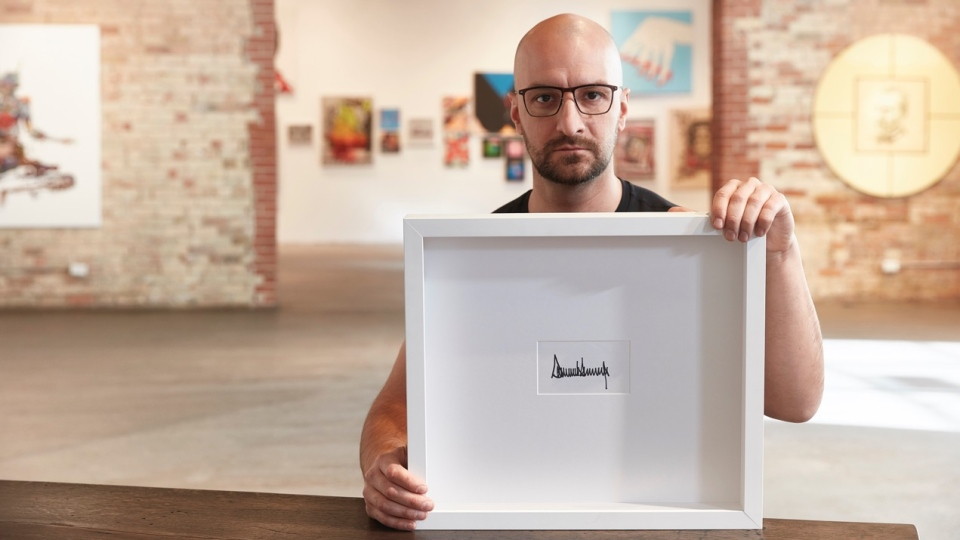 Artist Peter Andrew Lusztyk holds up his framed signature from Donald Trump at the Only One Gallery in Toronto.