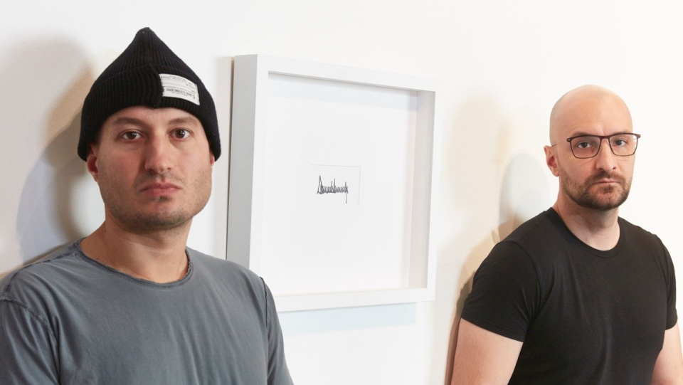 Only One Gallery owner Cais Mukhayesh, left, and Peter Andrew Lusztyk pose with a framed signature from Donald Trump in Toronto.