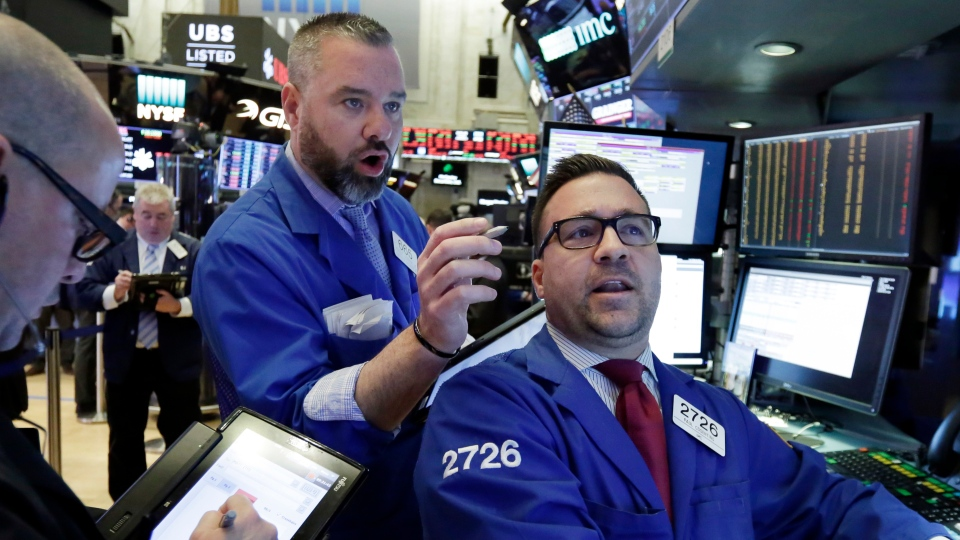 Trader Kevin Lodewick, center, and specialist Paul Cosentino, right, work on the floor of the New York Stock Exchange, Tuesday, Feb. 6, 2018. (AP Photo/Richard Drew)