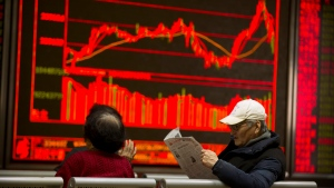 A Chinese investor reads a newspaper while monitoring stock prices at a brokerage house in Beijing, Wednesday, Feb. 7, 2018. (AP Photo/Mark Schiefelbein)