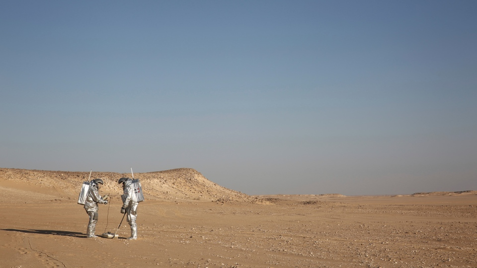 In this Feb. 7, 2018, photo, two scientists test space suits and a geo-radar for use in a future Mars mission in the Dhofar desert of southern Oman. (AP Photo/Sam McNeil)