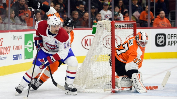 Philadelphia Flyers goalie Brian Elliott (37) looks for the puck as Montreal Canadiens' Tomas Plekanec (14) skates around the net in front of Andrew MacDonald during the third period of an NHL hockey game, Thursday, Feb. 8, 2018, in Philadelphia. The Flyers won 5-3. (AP Photo/Derik Hamilton)