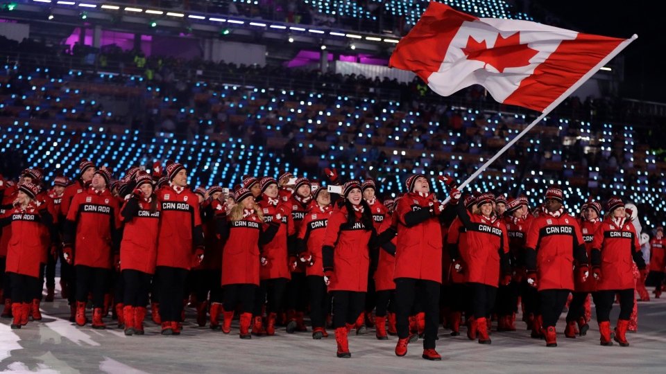 Tessa Virtue and Scott Moir bring in the flag of Canada during the opening ceremony of the 2018 Winter Olympics in Pyeongchang, South Korea, Friday, Feb. 9, 2018. (AP Photo/Petr David Josek)
