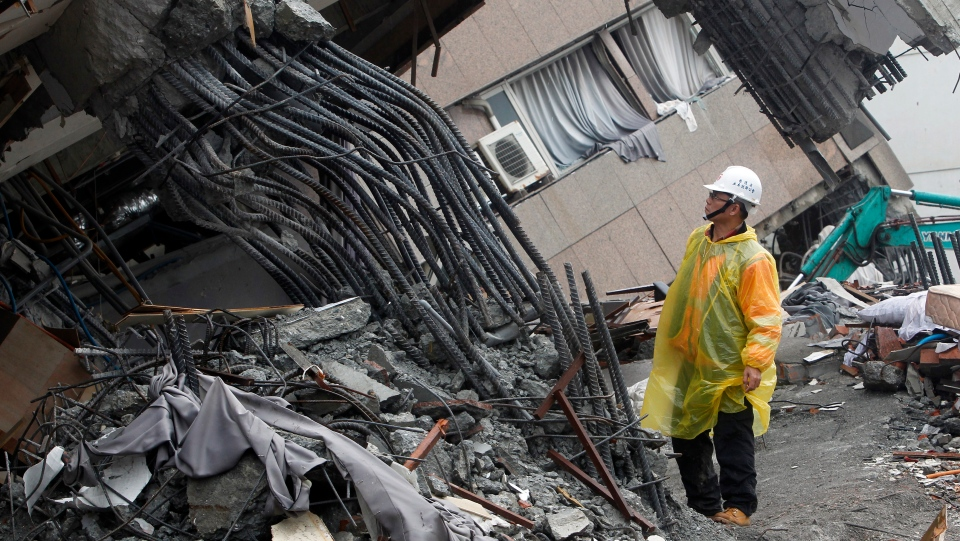In this Feb. 8, 2018 photo, an official inspects the failed rebar foundation pillars during a continued search operation at an apartment building collapsed after a strong earthquake in Hualien County, eastern Taiwan. (AP Photo/Chiang Ying-ying, File)