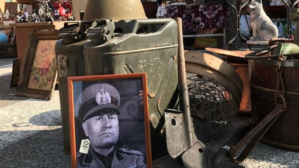 In this photo taken on Feb. 19, 2017 a picture of late dictator Benito Mussolini is displayed at an open air antiques market in Soave, neat Verona, Italy. Racist and anti-Semitic expressions have been growing more bold, widespread and violent in Italy. (AP Photo/Colleen Barry)