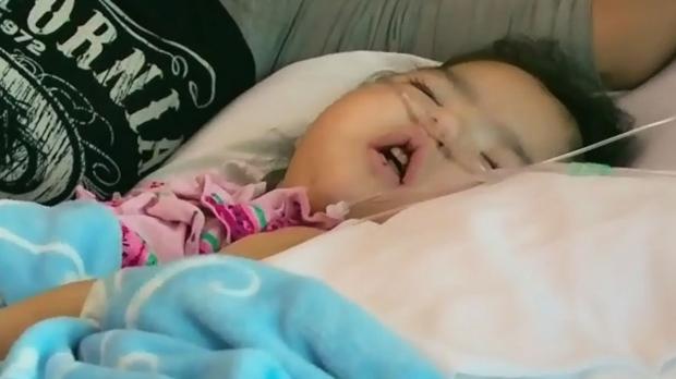 Four-year-old Aurora Sky Brandi Ledoux is pictured on life support in hospital, beside grandmother Josie Ledoux. (CTV Saskatoon)