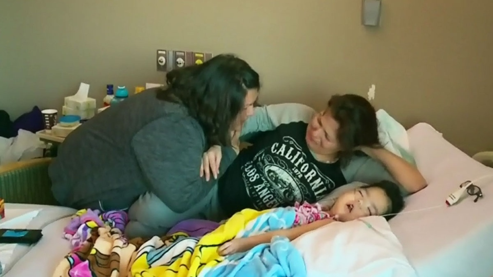 Josie Ledoux (second from right) is comforted by a family member at the bedside of her granddaughter, four-year-old Aurora Sky. (CTV Saskatoon)