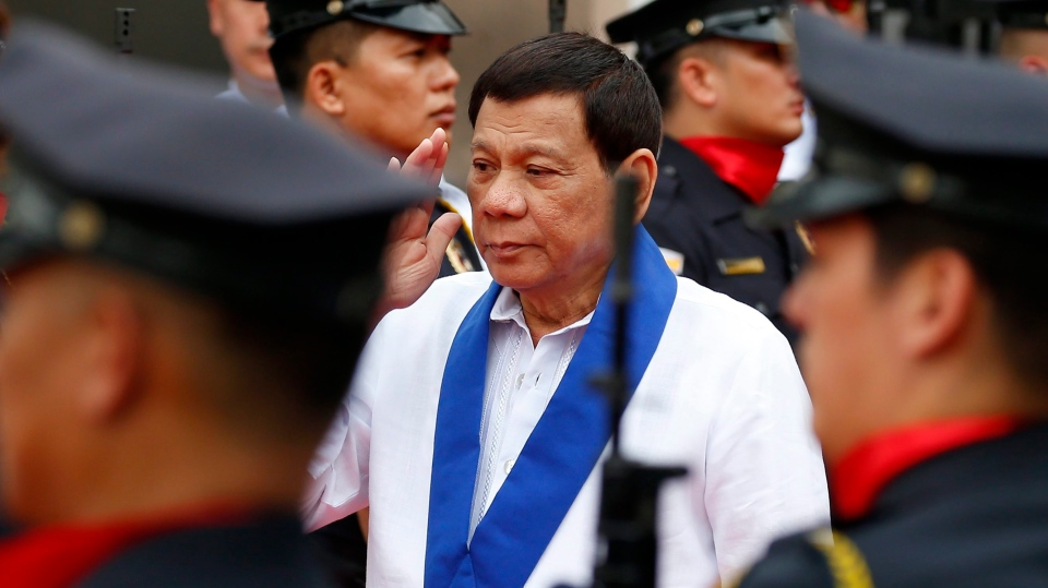Philippine President Rodrigo Duterte salutes customs police as he arrives to witness the destruction of a fleet of 20 used luxury cars and SUVs as part of the 116th anniversary celebration of the Bureau of Customs in Manila, Philippines Tuesday, Feb. 6, 2018. (AP Photo/Bullit Marquez)