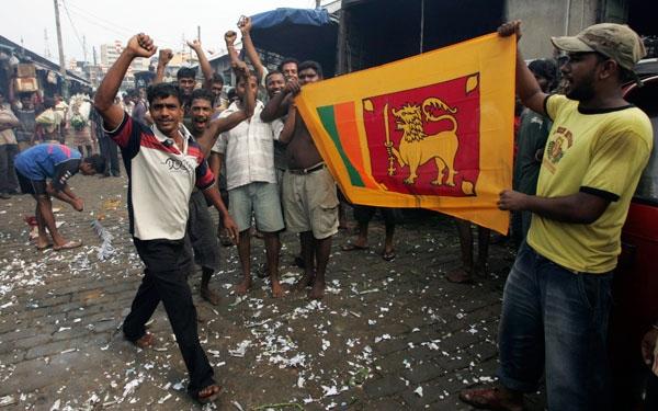 Sri Lankans display a national flag after President Mahinda Rajapaksa declared victory over the Tamil Tiger rebels in Colombo, Sri Lanka, Sunday, May 17, 2009.  (AP / Eranga Jayawardena)