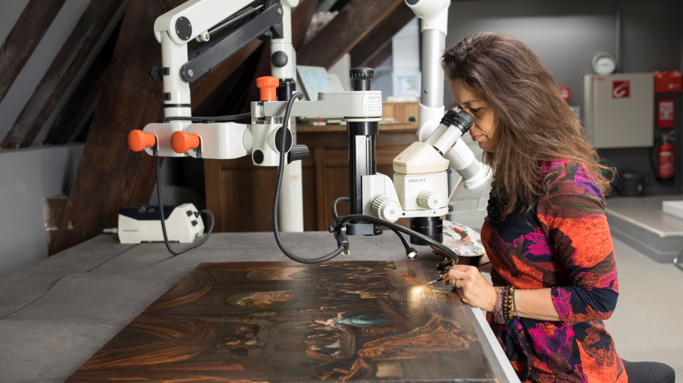 "In this undated photo, conservation expert Sabrina Meloni examines the artwork ""The Mocking of Samson."" (Ivo Hoekstra / Mauritshuis Museum via AP)"