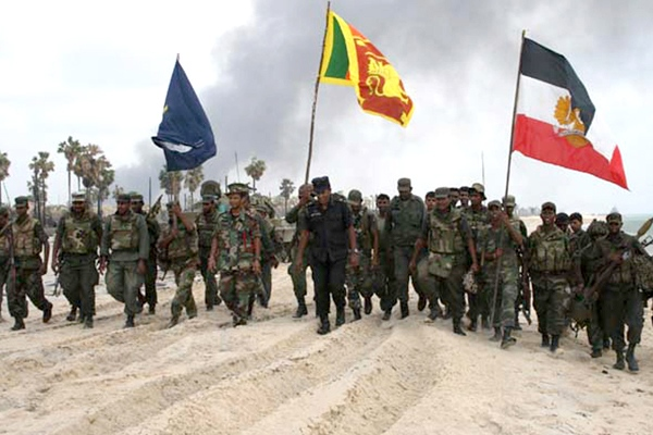 A handout photograph provided by Sri Lanka's army, dated Saturday, May 16, 2009, shows soldiers carrying the national flag and unit flags at a site they say is the last rebel stronghold in Kariyalamullivaikkal, Sri Lanka. (AP / Sri Lanka Army)