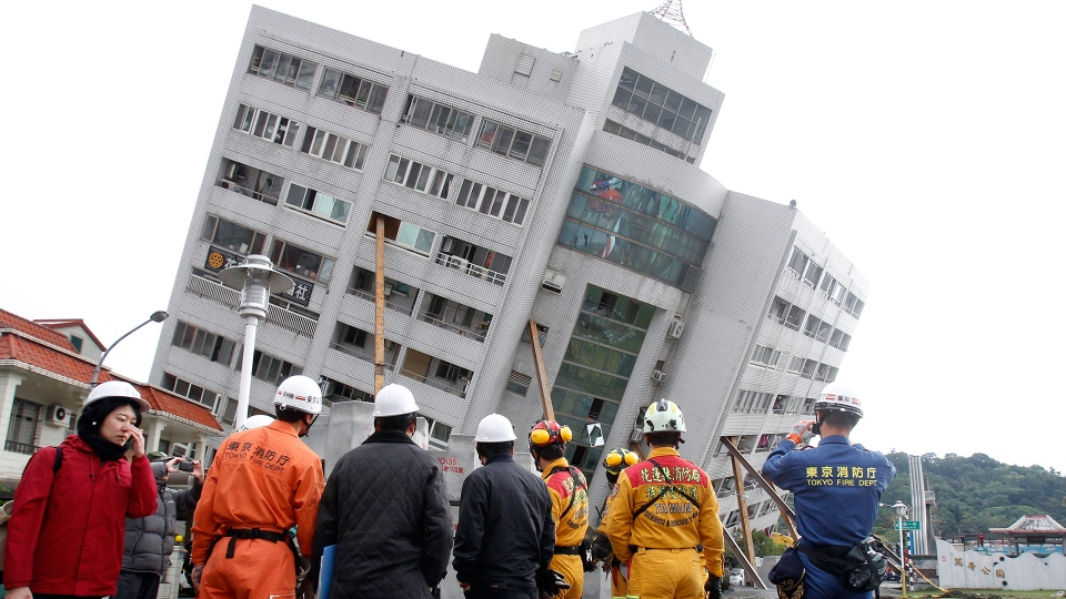 Rescuers from Japan join the searching operation at an apartment building collapsed after a strong earthquake in Hualien County, eastern Taiwan, Friday, Feb. 9, 2018. (AP / Chiang Ying-ying)