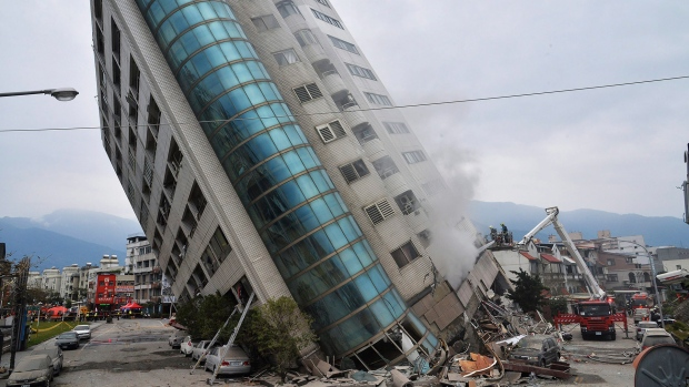 A residential building leans on a collapsed first floor following an earthquake, in Hualien, southern Taiwan, Wednesday, Feb. 7, 2018. (Central News Agency via AP)
