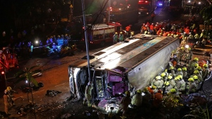 Firemen hurry to try to remove injured passengers from a double-decker lying on its side in Hong Kong, Saturday, Feb. 10, 2018. A double-decker bus crashed in a Hong Kong suburb on Saturday evening, killing 18 people and injuring dozens more, authorities in the southern Chinese city said. (Apple Daily via AP)