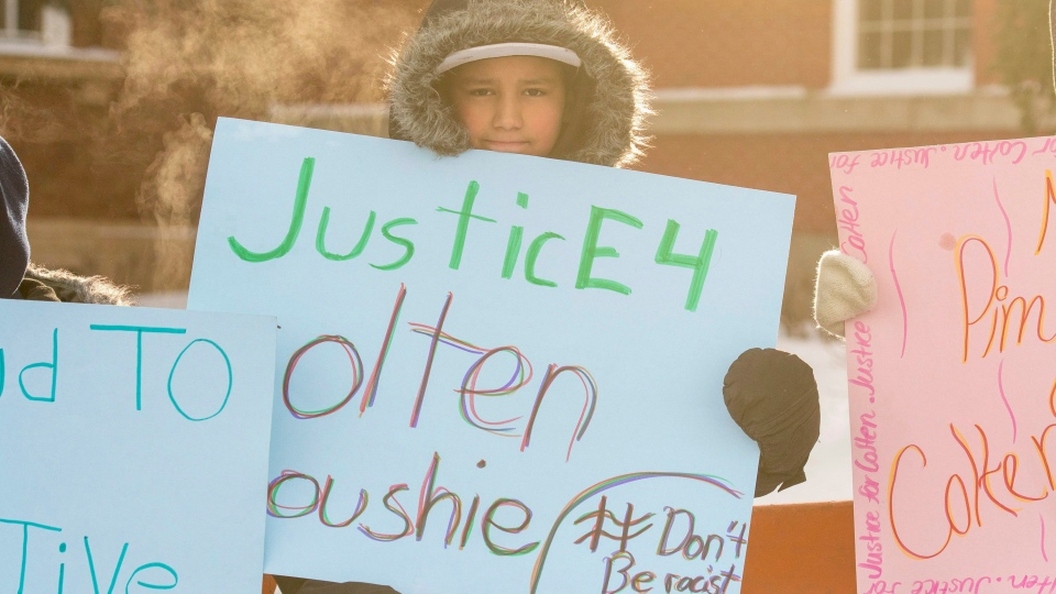 Grade 7 and 8 students from the Piyesiw Awasis School on the Thunderchild First Nation hold signs outside of the Court of Queen's Bench on the day of closing arguments in the trial of Gerald Stanley, the farmer accused of killing 22-year-old Indigenous man Colten Boushie, in Battleford, Sask. on Thursday, February 8, 2018. THE CANADIAN PRESS/Liam Richards