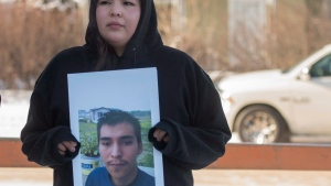 Krissa Baptiste holds a picture of her cousin of Colten Boushie, during a lunch recess on the day of closing arguments in the trial of Gerald Stanley, the farmer accused of killing 22-year-old Indigenous man Colten Boushie, in Battleford, Sask. on Thursday, February 8, 2018. THE CANADIAN PRESS/Liam Richards