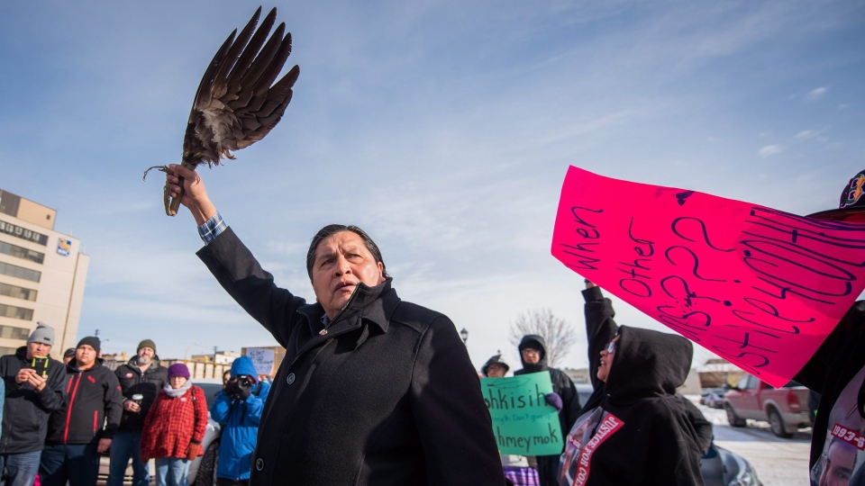 Colten Boushie's uncle Alvin Baptiste raises an eagle's wing as demonstrators gathered outside of the courthouse in North Battleford, Sask., on Saturday, February 10, 2018. (THE CANADIAN PRESS/Matt Smith)
