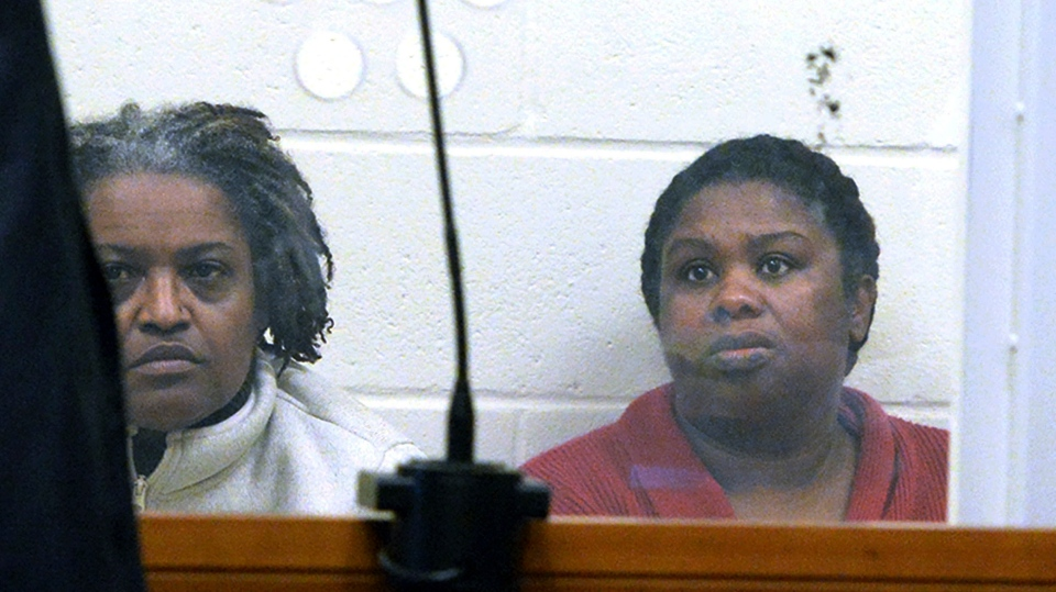 In this Feb. 1, 2018 file photo, sisters Rachel Hilaire and Peggy LaBossiere sit in Brockton District Court in Bridgewater, Mass., charged with tying down and burning a 5-year-old girl, permanently disfiguring her, in a voodoo ritual meant to rid her of a demon causing her to misbehave, police said. (Marc Vasconcellos/Enterprisenews.com via AP, Pool, File)
