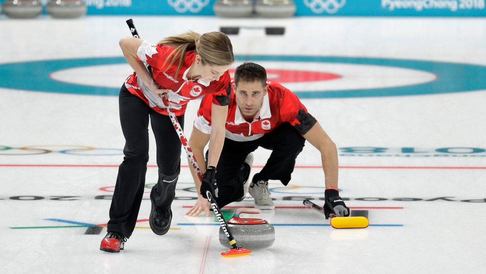 Canada's Kaitlyn Lawes, left, sweeps ice as John Morris shouts instructions during their mixed doubles semi-final match against Norway at the 2018 Winter Olympics in Gangneung, South Korea, Monday, Feb. 12, 2018. Canada won. (AP Photo/Aaron Favila)