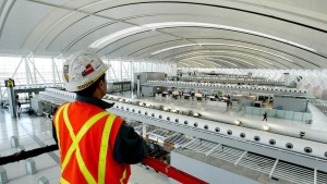 In this file photo, an Aecon Construction scissor lift operator looks at Toronto Pearson International Airport's Terminal 1 check-in area from above the scissor lift on Tuesday Dec. 2, 2003. CANADIAN PRESS/AP, Tobin Grimshaw
