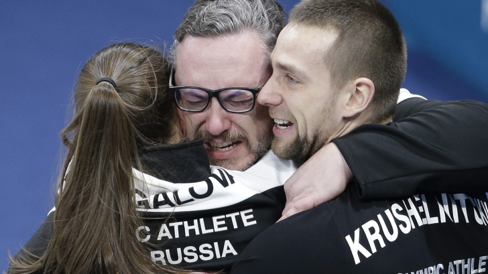 Russian coach, Vasily Gudin, centre, embraces Russian curlers Aleksandr Krushelnitckii, right, and Anastasia Bryzgalova after winning the bronze in mixed doubles curling against Norway at the 2018 Winter Olympics, on Feb. 13, 2018. (Aaron Favila / AP)