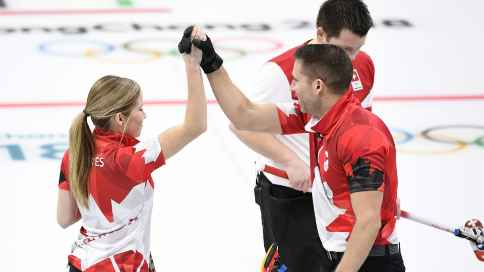 Canada's Kaitlyn Lawes and teammate John Morris hold hands during mixed doubles gold-medal curling action on Feb. 13, 2018. (Nathan Denette / THE CANADIAN PRESS)