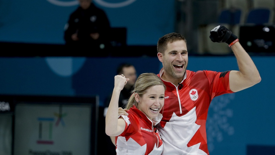 Kaitlyn Lawes, left, and John Morris celebrate winning the mixed doubles final curling match against Switzerland, on Feb. 13, 2018. (Natacha Pisarenko / AP)