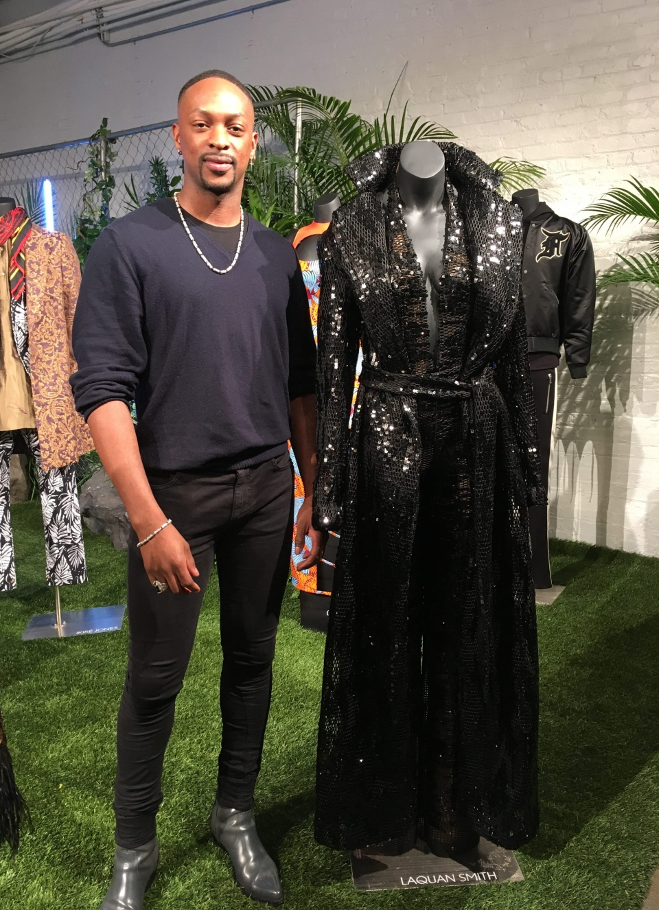 Fashion designer LaQuan Smith stands with his jumpsuit and trench coat created for a small collection inspired by the film 'Black Panther' on Monday, Feb. 12, 2018 in New York.  (AP Photo/Leanne Italie)