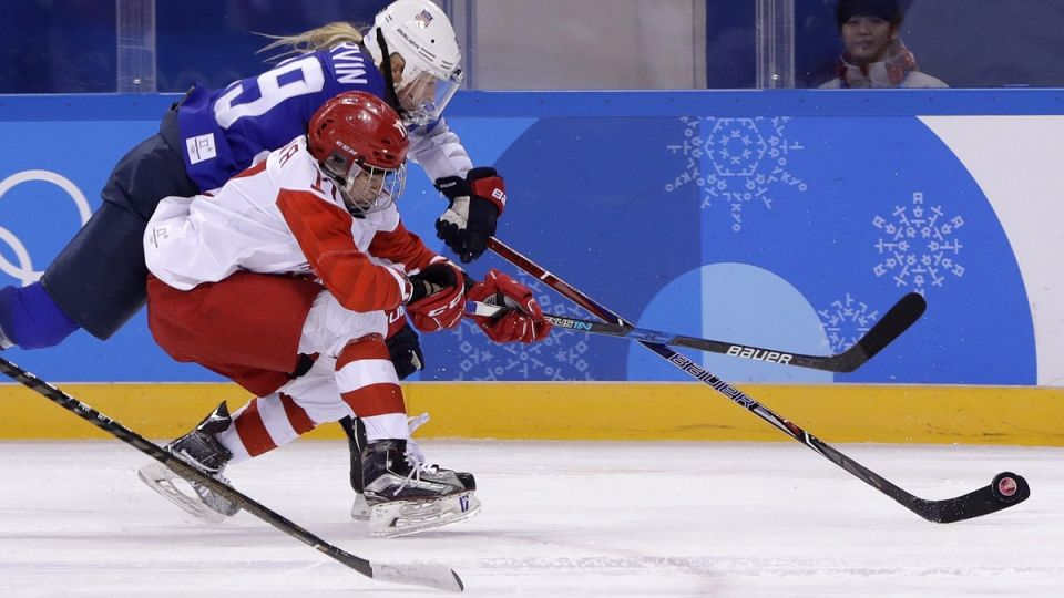 Gigi Marvin (19), of the United States, and Russian athlete Fanuza Kadirova (17) battle for the puck in Gangneung, South Korea, on Feb. 13, 2018. (Matt Slocum / AP)