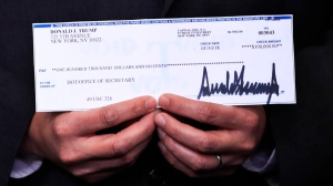 A $100,000 cheque from U.S. President Donald Trump's quarterly salary, donated to the Department of Transportation, is presented during the daily press briefing in the Brady press briefing room at the White House, in Washington, Tuesday, Feb. 13, 2018. (Manuel Balce Ceneta/AP Photo)